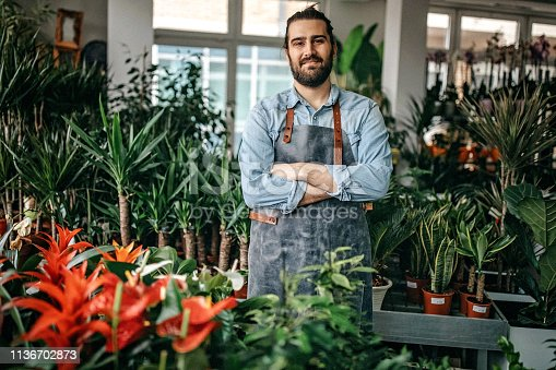 Proud man standing out in flower shop