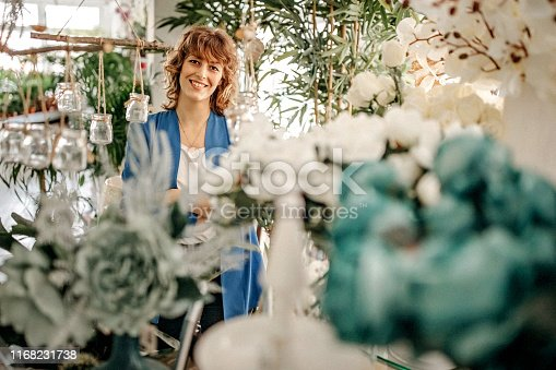 Proud woman standing out in flower shop