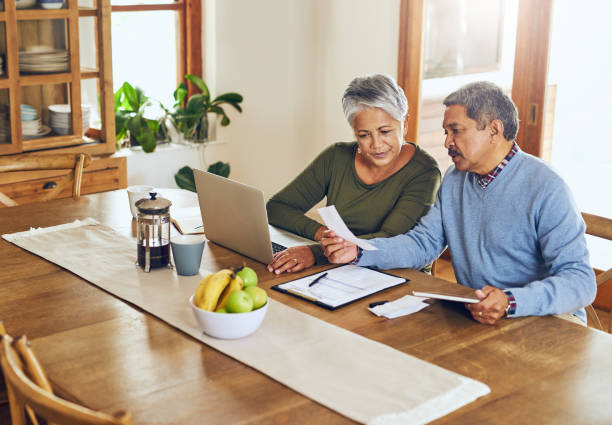 This should be the return on our investment Shot of a mature couple managing their paperwork together at home retirement stock pictures, royalty-free photos & images