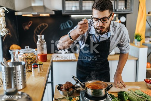 Photo of chef tasting delicious lunch he is preparing in the kitchen