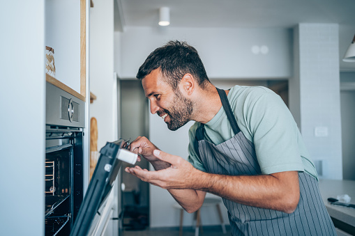 Handsome young man preparing healthy meal in modern kitchen. Smiling man checking food in the oven.