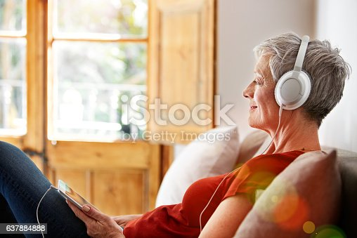 Shot of a mature woman sitting on her sofa listening to music on a digital tablet