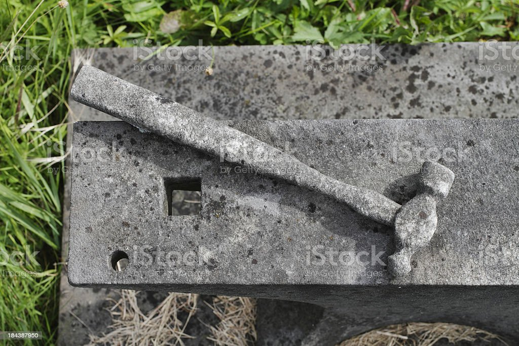 Blacksmith's hammer and anvil commemoration in stone tombstone royalty-free stock photo