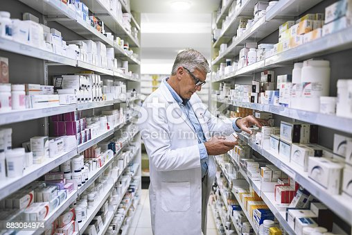 Shot of a focused mature male pharmacist making notes of the medication stock on the shelves in a pharmacy