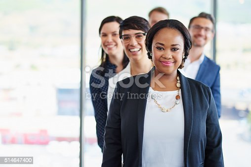 Portrait of a team of diverse colleagues standing together in a line at the office