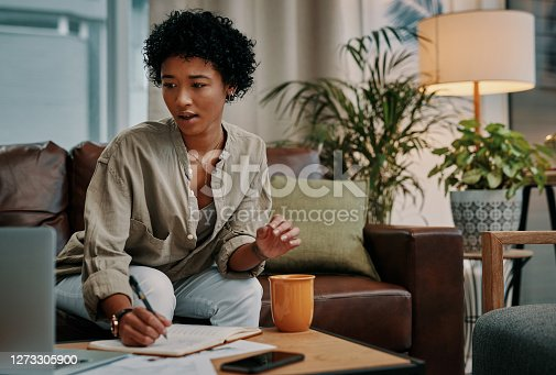 Shot of a woman making notes while using her laptop at home