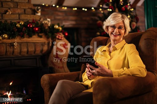 Smiling senior woman sitting in a living room with Christmas decorations while using her mobile phone