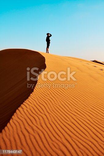 Shot of a young man standing on a hill in the Namibian Desert