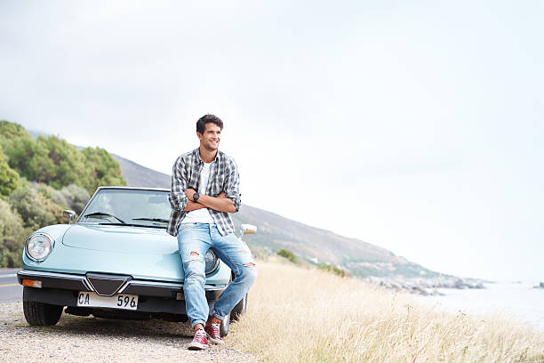 This view is breathtaking... Handsome young man resting on a hilltop after taking a scenic drive leaning stock pictures, royalty-free photos & images