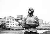 African american man standing outdoors after his training in the city and smiling. He have his arms crossed.