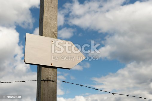 Directional wooden sign on a barbed wire fence
