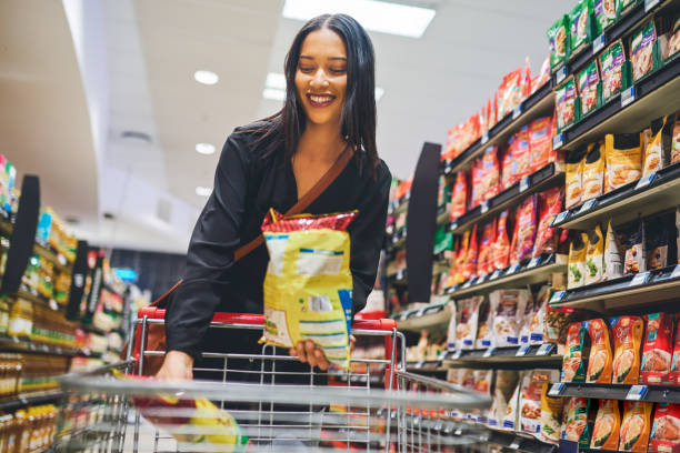 This will go well with tonight's movie Shot of a young woman shopping in a grocery store snack aisle stock pictures, royalty-free photos & images