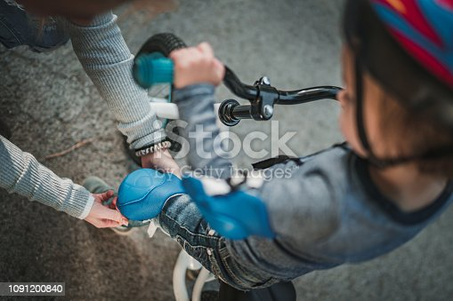 Close up of unrecognizable mother adjusting son's kneepad before bicycle ride.
