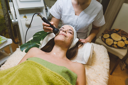 Young beautiful caucasian women at a beauty salon, having a day for herself getting pampered. Customer is getting facial mask done, to moisturize her skin. Beautician has already applied face mask and is now using a facial care machine, which will help to moisturize the skin trough the mask and calm the redness, moving the machine in circular motion.