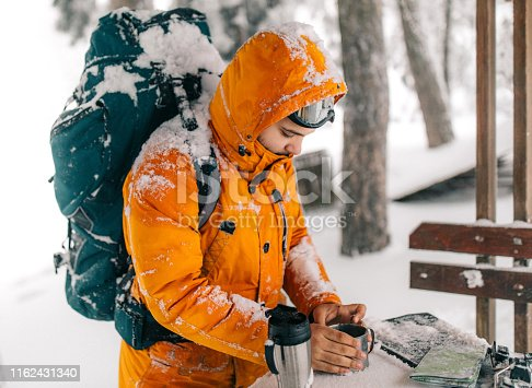 Man rests for a long walk through the snowy mountain