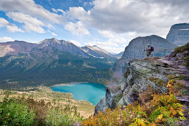 hiker looking down on lower grinnell lake - us glacier national park stock pictures, royalty-free photos & images