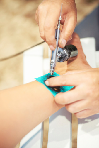 Cropped shot of a a person getting an ankle tattoo