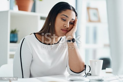 Shot of a young businesswoman looking bored while sitting at a desk in an office
