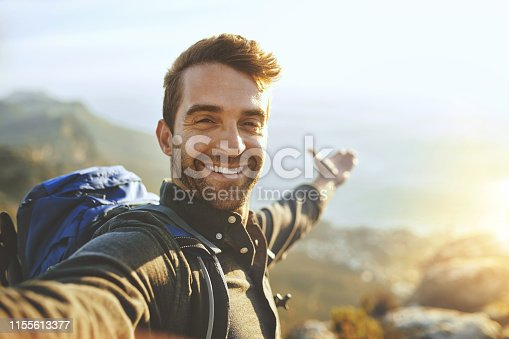 Shot of a young man taking selfies while hiking up a mountain
