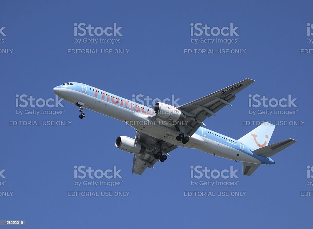 Thomson Holidays aeroplane in flying with landing gear down stock photo