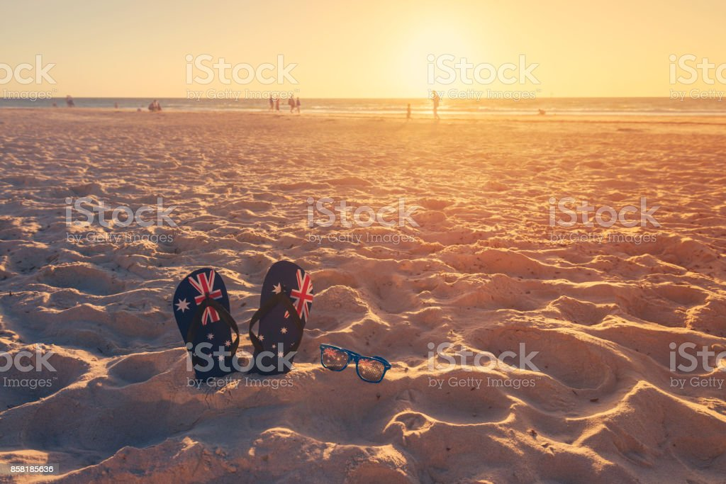 Thongs and sunglasses on beach sand stock photo