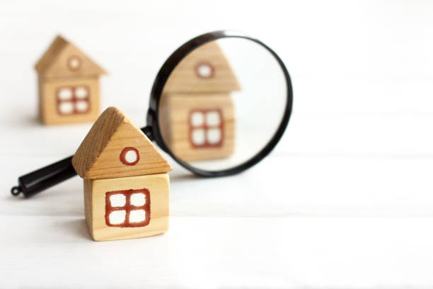 thorough study of real estate offers Wooden houses and magnifying glass for inspection symbiotic relationship stock pictures, royalty-free photos & images