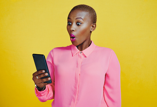 Cropped shot of an attractive young woman looking surprised while using her cellphone in studio against a yellow background