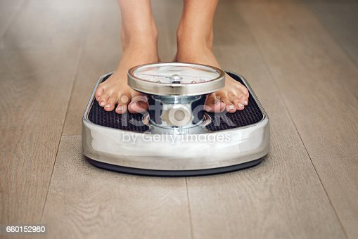 Closeup shot of a young woman weighing herself on a scale at home