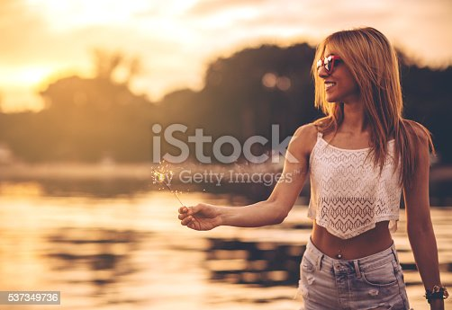 Young woman dancing on the beach. Wearing boho style clothing and holding sparklers. Enjoying in sunset.