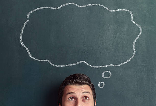 Thought bubble Young man is thinking in front of blackboard. thought bubble stock pictures, royalty-free photos & images
