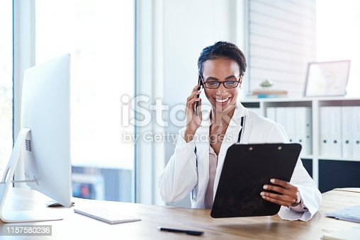 Shot of a young doctor using a smartphone going over paperwork in her consulting room