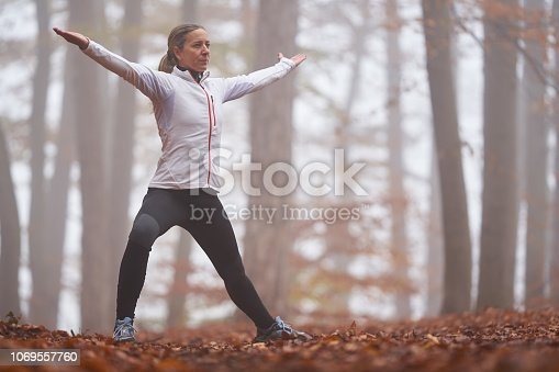 45 year old woman stretching and doing gymnastics in autumn forest foggy bad weather conditions cold october or november look