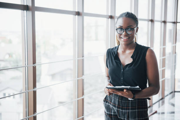 A thoughtful African American business woman wearing glasses holding documents A thoughtful African American business woman wearing glasses holding documents. politics stock pictures, royalty-free photos & images
