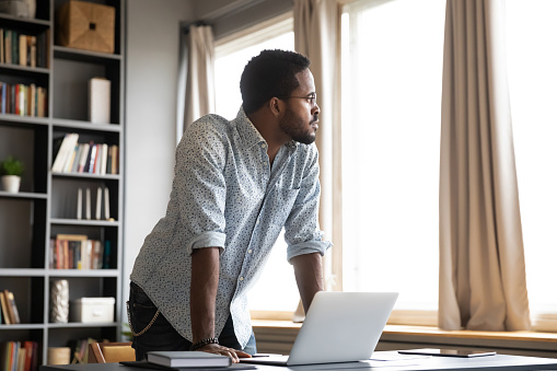 Young thoughtful african american businessman leaning on table with laptop, looking away. Millennial hipster biracial entrepreneur thinking of problem solution, future challenges in office or home.