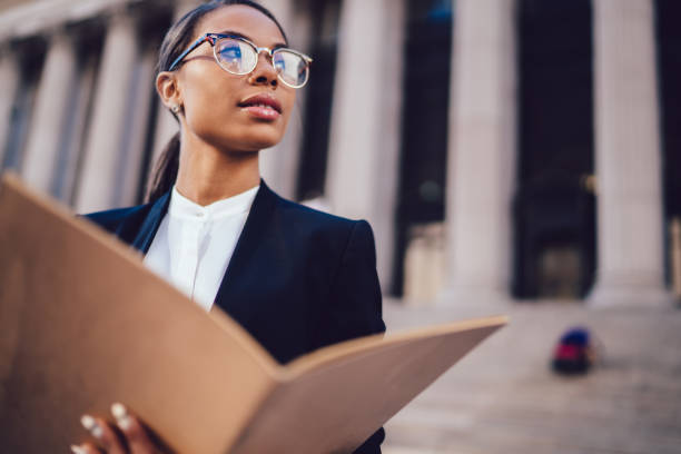 Thoughtful African American businesswoman in optical spectacles holding documents looking away while standing in urban setting with copy space. Female dark skinned student of high economic university stock photo