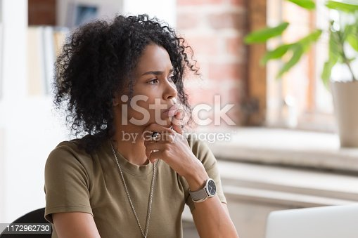 Thoughtful doubt African American businesswoman or student with hand under chin feeling uncertain, thinking about project or difficult task, manager pondering business strategy, planning, close up