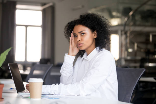 Thoughtful african businesswoman looking away thinking of business problem solution Serious thoughtful african business woman sitting at office desk with laptop looking away thinking of problem solution, pensive millennial black female searching new idea at work lost in thoughts disillusioned stock pictures, royalty-free photos & images