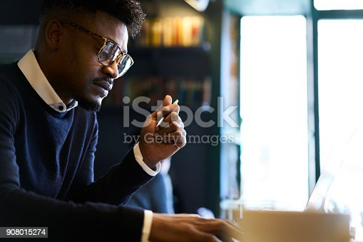 istock Thoughtful afro american male popular writer working on creation his new book searching inspiaration while spending time in cafe noting best ideas finishing story in time to confirm in bookhouse 908015274