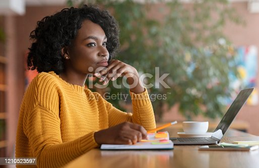 Thoughtful afro young woman looking for new job online, using laptop at cafe, taking notes, side view, copy space