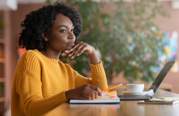 Thoughtful afro woman looking for new job online Thoughtful afro young woman looking for new job online, using laptop at cafe, taking notes, side view, copy space reflection stock pictures, royalty-free photos & images