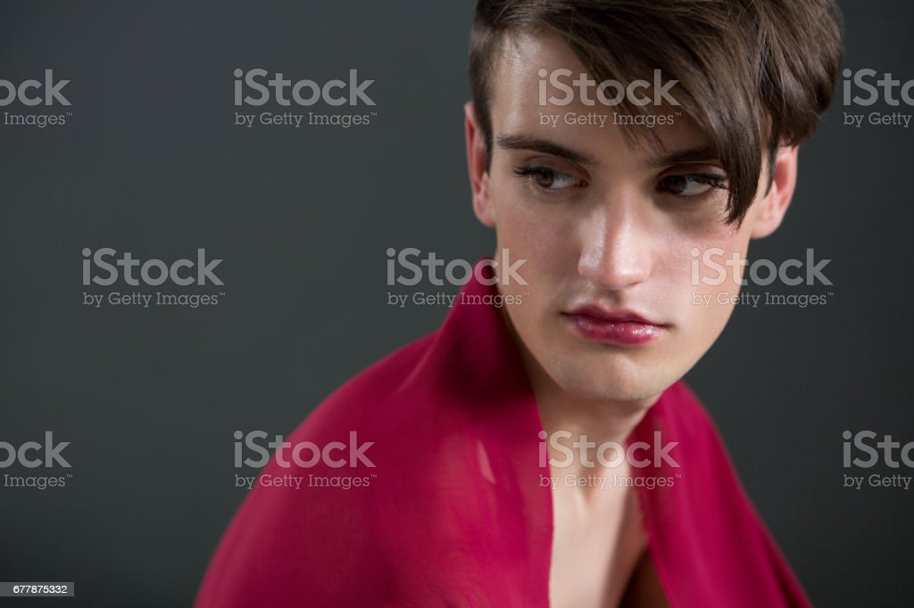 Thoughtful androgynous man wrapped in red clothes royalty-free stock photo
