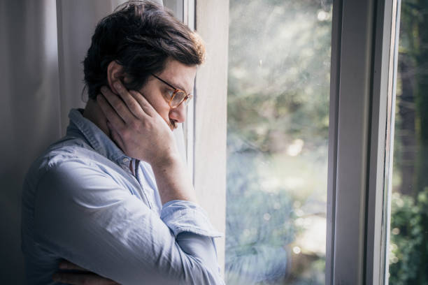 Thoughtful anxious guy looking out the window stock photo