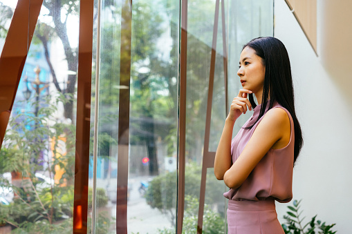 Asian businesswoman with hand on chin looking through large window at work, contemplation, aspiration, ideas