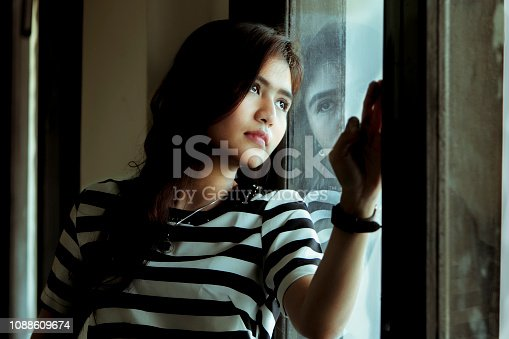 istock thoughtful asian girl standing at window 1088609674