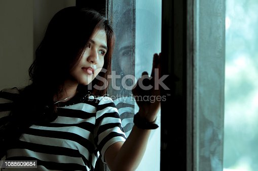 istock thoughtful asian girl standing at window 1088609684