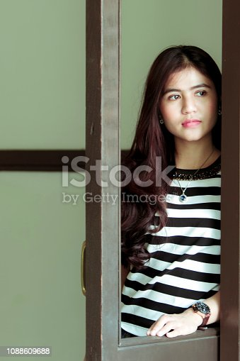istock thoughtful asian girl standing at window 1088609688