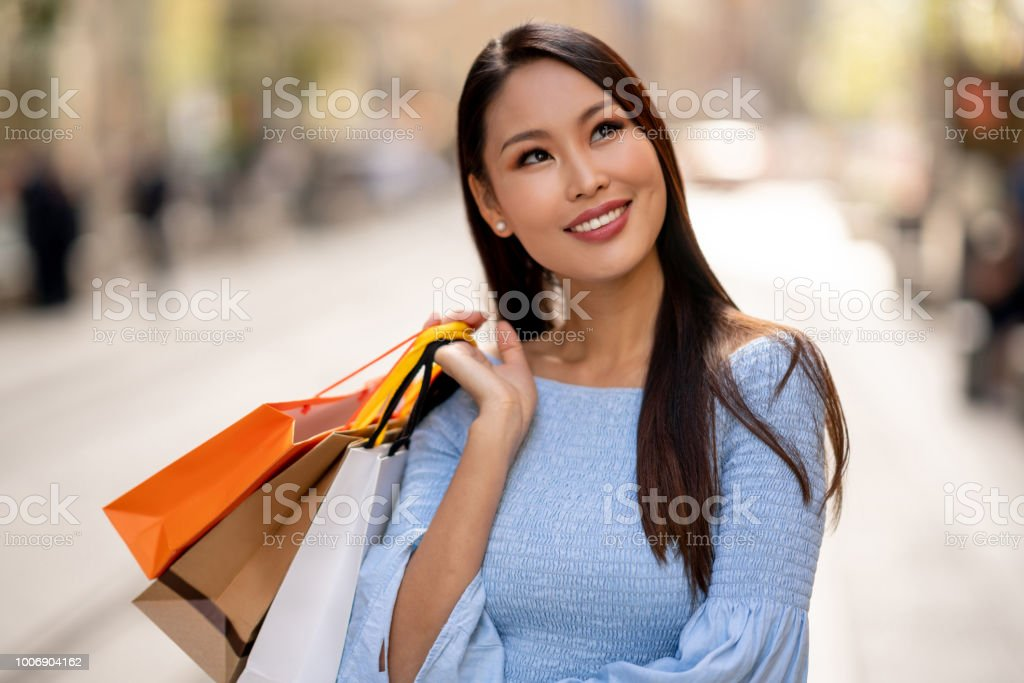 Portrait of a beautiful thoughtful Asian shopping woman on the street...