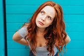 Thoughtful attractive redhead woman bending forwards and looking up to the side with a contemplative expression against a blue wall