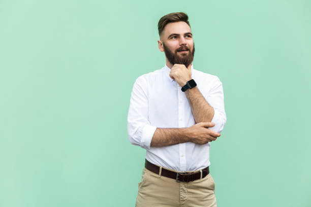 Thoughtful bearded businessman looking away while standing against light green wall. Studio shot stock photo