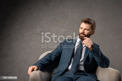 1081599130 istock photo thoughtful bearded businessman sitting in armchair 1081599036